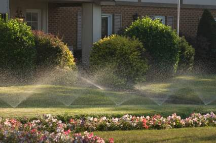 Residential Irrigation: Sprinklers watering a home lawn.